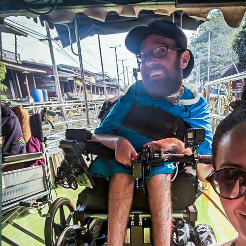 Ean using an accessible riverboat to visit Thai floating markets