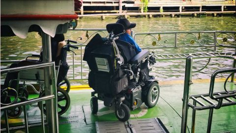 Ean embarking on a riverboat in Thailand